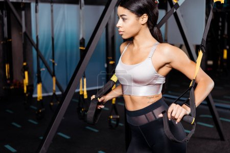 Sportive girl working out with resistance bands in sports centre