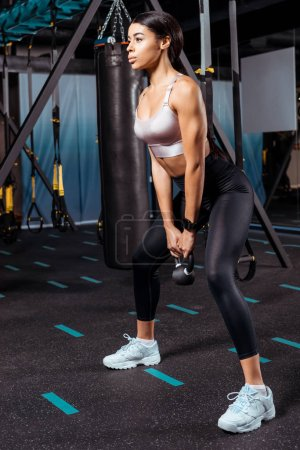 Wonderful athletic girl squatting with dumbbells in sports gym