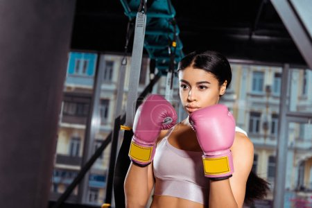 Photo for Attractive strong girl in protective gloves practicing boxing in gym - Royalty Free Image