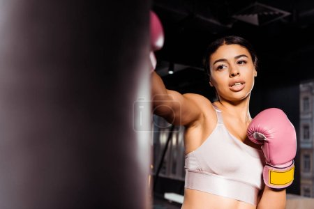 Attractive strong girl in pink boxing gloves practicing boxing in gym