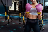 Partial view of  female boxer in pink boxing  gloves practicing boxing in gym