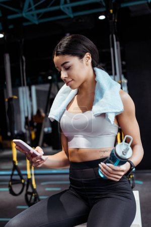 Beautiful sportive girl using digital device while holding sport bottle in gym