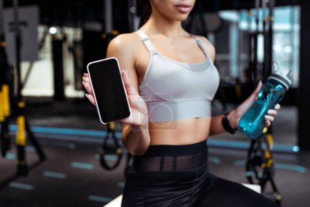 Partial view of sportive woman holding smartphone in fitness gym