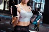 Cropped view of sportive woman holding smartphone and sport bottle in fitness gym
