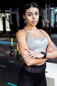 Beautiful sportive girl with crossed arms llooking at camera while standing in fitness gym