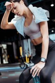 Tired attractive sportive girl with towel and sport bottle in fitness gym