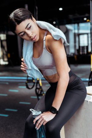 Beautiful strong girl with towel and sport bottle in fitness gym