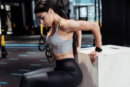 Beautufil active sportive girl exercising in fitness gym