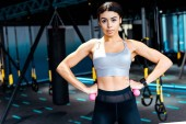 Sportive girl standing akimbo with dumbbells in fitness gym