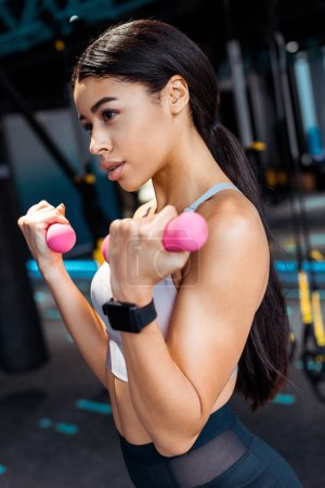 Photo for Attractive Strong girl working out with dumbbells in fitness gym - Royalty Free Image