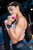 Sportive girl training with dumbbells in fitness gym
