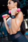 Close up of strong sportive girl working out with dumbbells in fitness gym