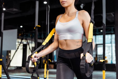 Cropped view of attractive sportive girl exercising with suspension straps in sports gym
