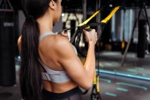 Back view of sportive girl training with resistance bands in sports gym