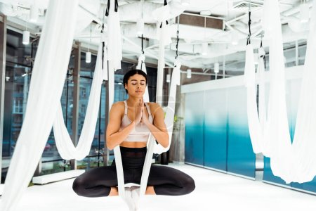 Girl practicing antigravity yoga in lotus position with namaste mudra gesture in light studio