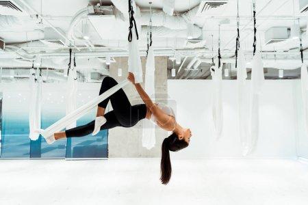 Attractive girl practicing antigravity yoga in inversion position in studio