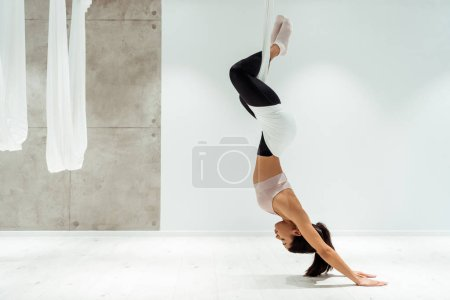 Photo for Sportive girl relaxing while practicing antigravity yoga and inversion position in yoga studio - Royalty Free Image