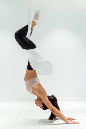 Attractive relaxed girl practicing antigravity yoga in upside down position in studio