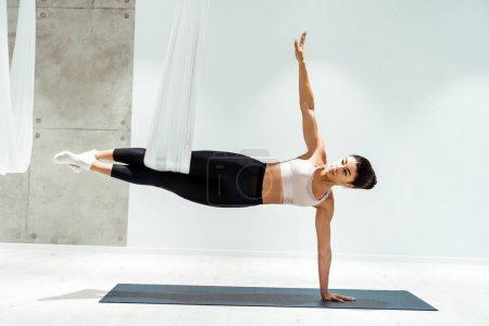 Attractive strong female practicing antigravity yoga in hammock in studio