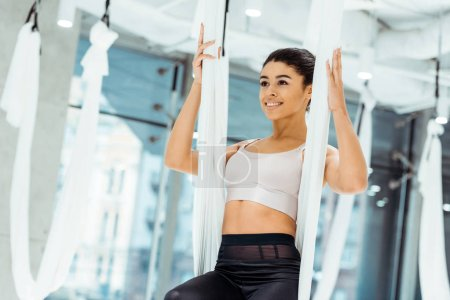 Smiling relaxed sportive girl practicing antigravity yoga in yoga studio