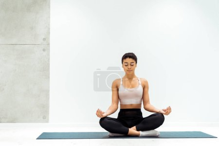Relaxed girl with closed eyes meditating in lotus position in yoga studio