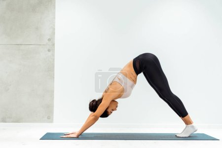 Relaxed girl practicing hatha yoga in yoga studio