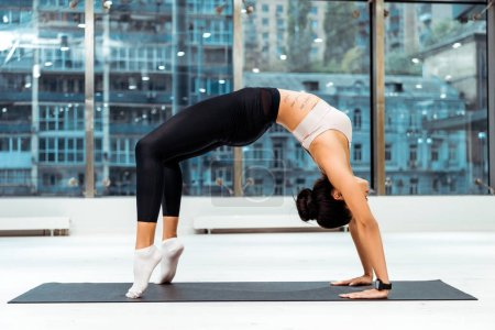 Photo for Sportive girl stretching in bridge pose on mat in fitness gym - Royalty Free Image