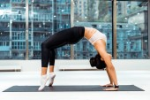 Sportive girl stretching in bridge pose on mat in fitness gym