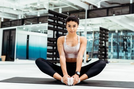 Wonderful young woman stretching in gym on fitness mat