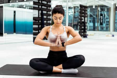 Attractive girl with closed eyes meditating in lotus position and namaste mudra gesture in yoga studio