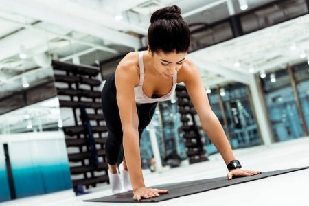 Photo for Attractive strong girl doing plank on mat in sports gym - Royalty Free Image
