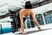 Attractive strong girl doing plank on mat in sports gym