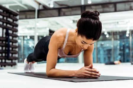 Photo for Beautiful sportive girl doing plank on mat  in fitness gym - Royalty Free Image