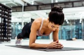 Beautiful sportive girl doing plank on mat  in fitness gym