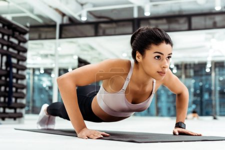 Photo for Wonderful young girl doing push ups on mat in fitness gym - Royalty Free Image