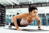 Wonderful young girl doing push ups on mat in fitness gym