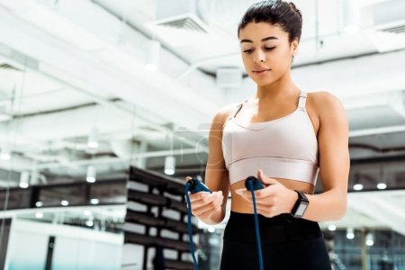 Photo for Attractive sportive girl holding skipping rope in fitness gym - Royalty Free Image