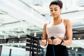 Attractive sportive girl holding skipping rope in fitness gym