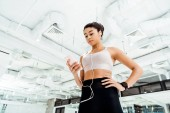Low angle view of beautiful sportive girl listening to music while standing in fitness gym