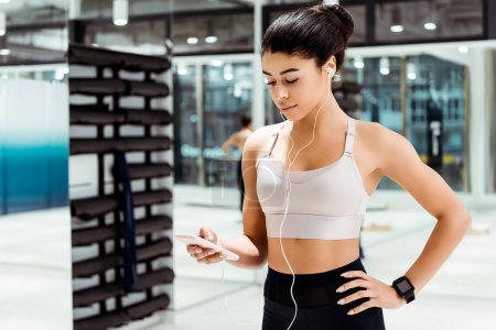 Photo for Attractive sportive girl listening to music while standing with hands on hip in fitness gym - Royalty Free Image