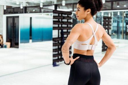 Beautiful strong girl in sportswear in fitness gym