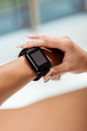 Partial view of girl using fitness tracker