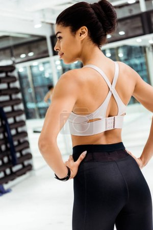 Attractive strong girl in sportswear standing with hands on hip in fitness gym