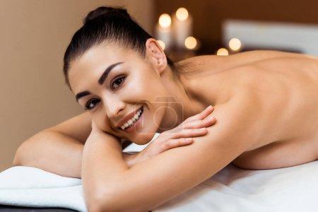 Photo pour Belle jeune femme couchée sur la table de massage et souriant à la caméra dans le spa - image libre de droit