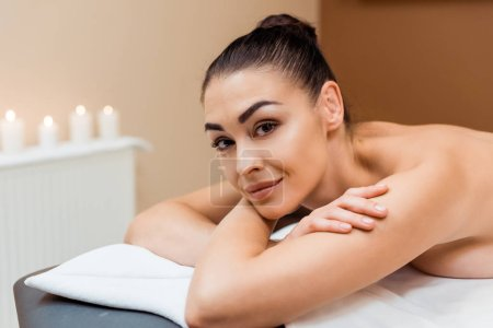 attractive young woman lying on massage table and smiling at camera in spa