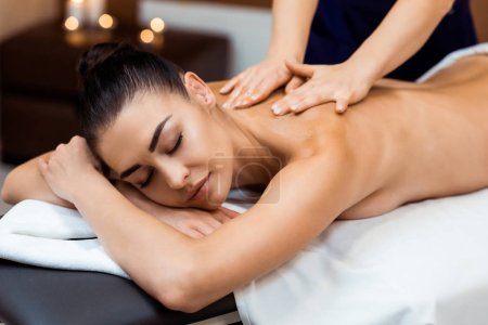 attractive young woman with closed eyes having massage therapy in spa