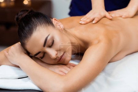 beautiful young woman with closed eyes having massage treatment in spa