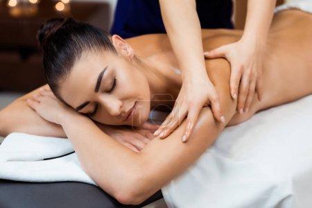 Photo pour Belle jeune femme avec les yeux fermés vu massage au spa - image libre de droit