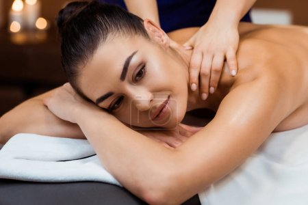 beautiful smiling young woman having massage in spa