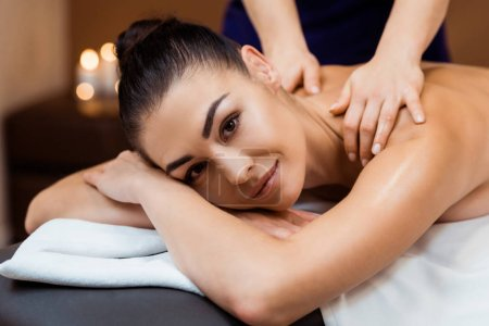 attractive young woman smiling at camera while having massage in spa salon